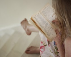 Little girl reading a book. Teaching children to read.